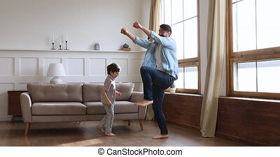 Young father dancing on heated wooden floor with small son.