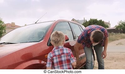 Young father demonstrate how to clean and wash the car's...