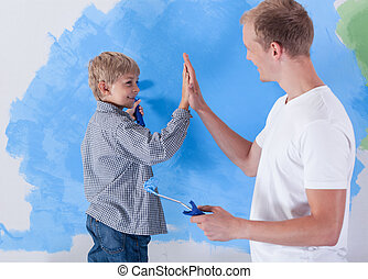 Young father giving high five to his little son during...