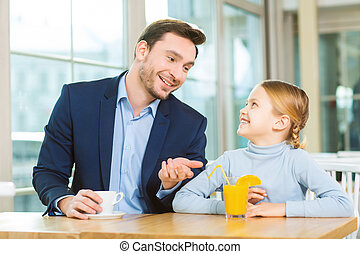 Young father having a conversation with curious daughter.