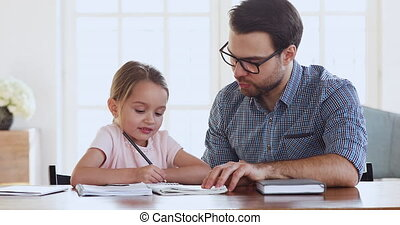 Young father helping little cute kid daughter with homework.