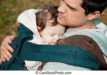father holding a little child in a backpack