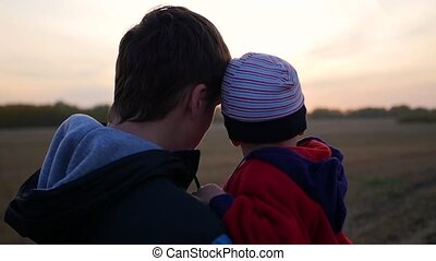 Young father holding his child on hands and watch the sunset. Tenderness and embrace of the beloved father. Outdoor activities