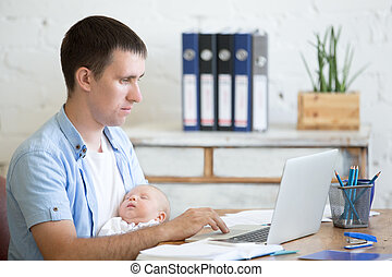 Young father holding newborn child and working on laptop