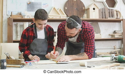 Dad is helping his son to mark up lines on wooden plank with...