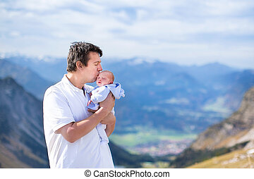Young father kissing his newborn baby son while trekking in the