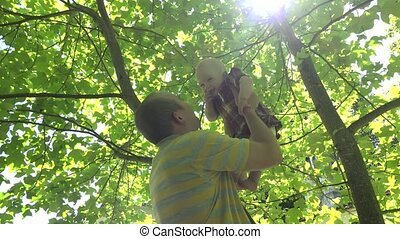 Young father lift his happy baby daughter under tulip tree in park. 4K