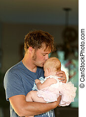 Young Father Lovingly Hugging and Kissing Baby Daughter