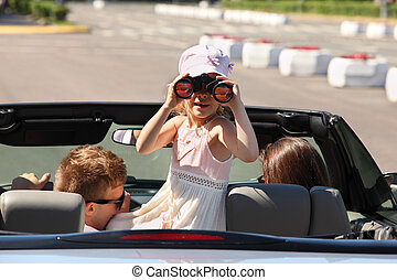 Young father, mother and daughter ride in convertible car; girl looks through binoculars back; focus on girl