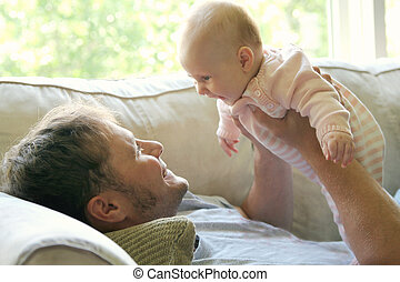 Young Father Playing with Newborn Baby Girl