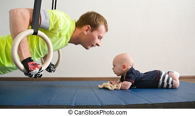 Young father pressed on the gymnastic rings. Next to him lie a little baby plays with a toy. Man kisses the child's forehead.