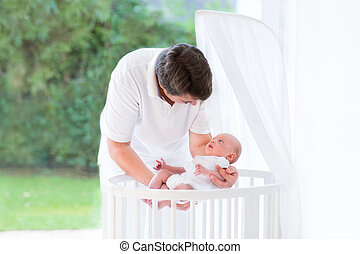 Young father putting his newborn baby into a white round crib ne