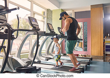 Young father running on racetrack in gym with his little son.