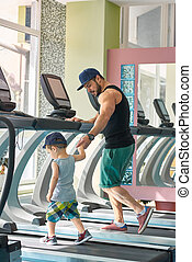 Young father running on racetrack in spacy gym with little son.
