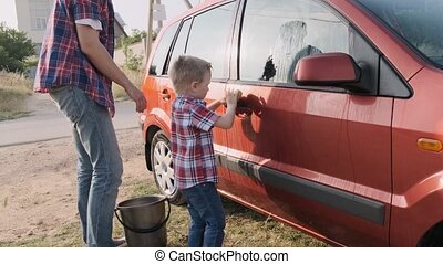 Young father shows his little cute kid how to wash their red...