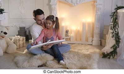 Young father sitting with daughter at fireplace and telling...