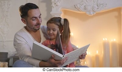 Young father sitting with daughter at fireplace and telling story on Christmas eve