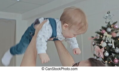 Young father throws baby into the air