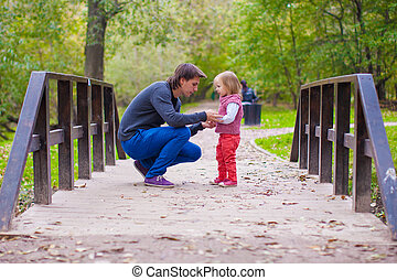 Young father walking with his little daughter in autumn park