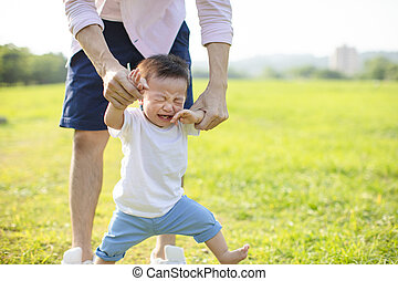 young father with crying baby in the park