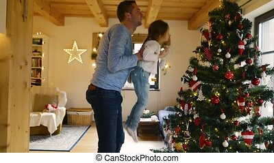 Young father with daugter decorating Christmas tree together...