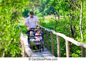 Young father with double stroller in a park - Young active...