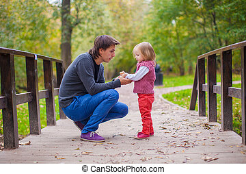 Young father with his cute little daughter in autumn park