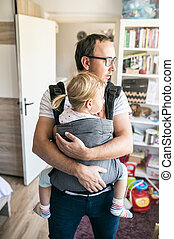 Young father with his daughter in baby carrier