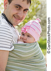 Young father with his five months daughter in sling