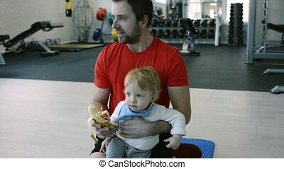 Young father with his little son in gym eating banana.
