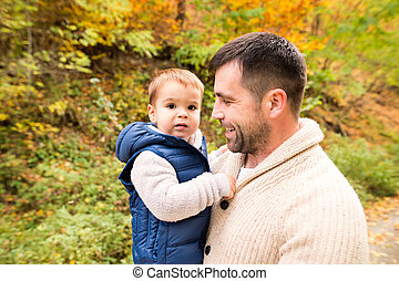 Young father with his son in autumn forest.