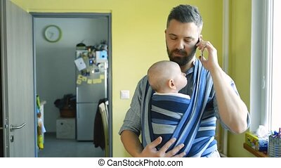 Young father with his son in sling with smart phone