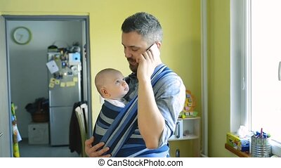 Young father with his son in sling with smart phone - Young...