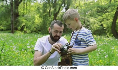 Young father with little boy with camera in summer park.