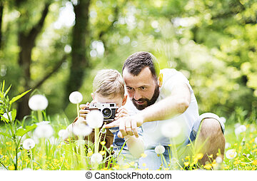 Young father with little boy with camera in summer park. -...