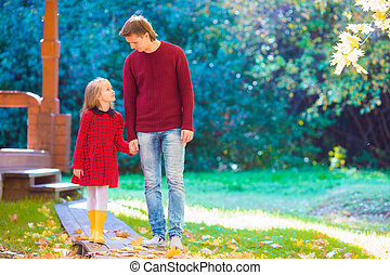 Young father with little daughter in autumn park outdoors