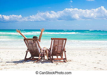 Young father with little daughter in beach chairs raised their hands up on the sea