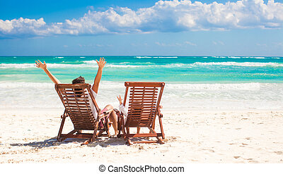 Young father with little daughter in beach chairs raised their hands up on white sand plage