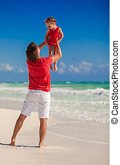 Young father with little girl having fun on the beach