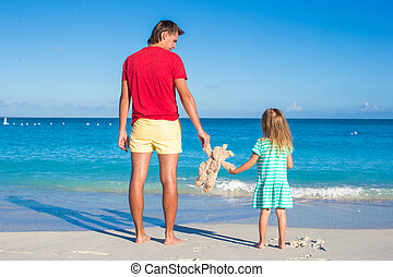 Young father with little girl holding a plush rabbit on exotic beach