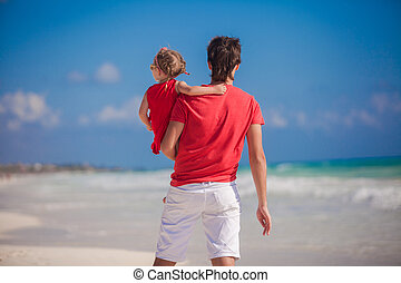 Young father with little girl look at the sea