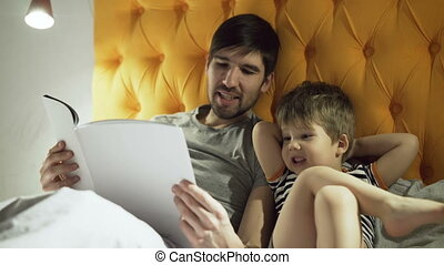 Young father with little son lying on bed at home and reading fairytale book before sleeping in evening