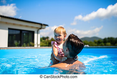 Young father with small daughter in swimming pool outdoors in backyard garden.