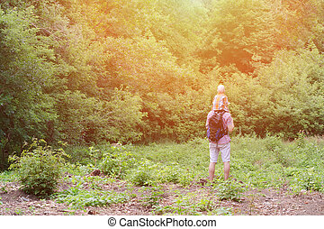 Young father with son on shoulders standing against a background of green forest. Back view. Sunlight.