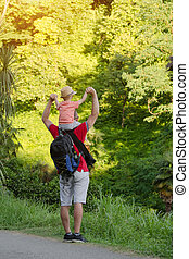 Young father with son on shoulders standing against a background of tropical green forest. Back view. Sunlight.