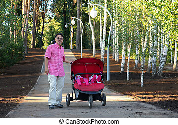 Young father with twin pram walking in the park