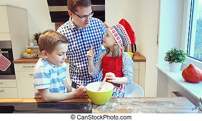 Young father with two happy children backing cookies in modern kitchen