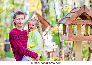 Young father witk little daughter feed the birds in autumn park outdoors