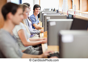 Young fellow students in an IT room with the camera focus on the background