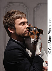 Young man hugging his jack Russell terrier dog